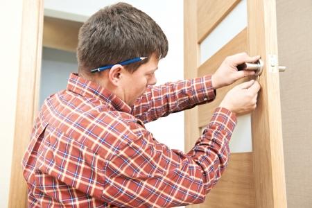 carpenter at door lock installation Фото со стока
