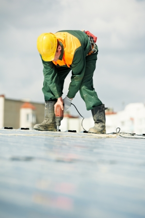 cladding tile: Worker builder roofer at metal profile work Stock Photo