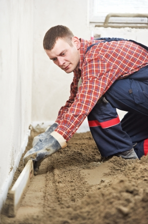 Plasterer concrete worker at floor work photo