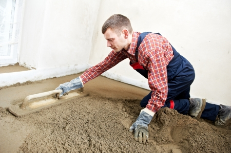 parget: Plasterer concrete worker at floor work Stock Photo