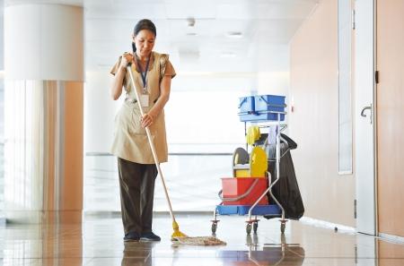 dweilen: Vrouw reinigen gebouw hal Stockfoto