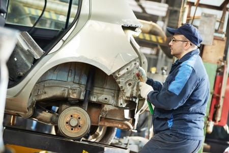 reparation automobile: homme de r�paration automobile aplatir voiture en m�tal du corps