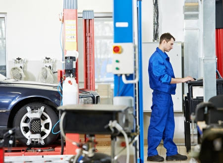 automobile workshop: car mechanic at wheel alignment with computer
