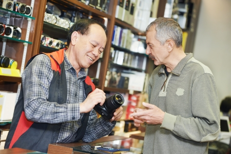 vendedores: Vendedor demostrando cámara de fotos al comprador