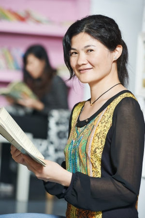 young chinese student girl with book in library photo