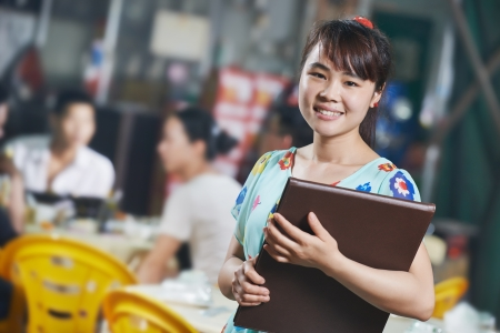 small business owner: Waitress chinese girl of restaurant with menu