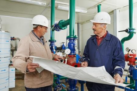 technicians: heating engineer repairman in boiler room Stock Photo