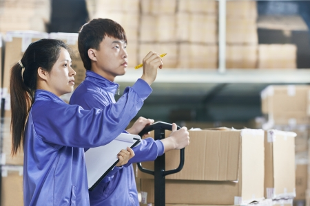warehouse equipment: two chinese workers in warehouse