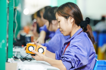 electronics industry: chinese male worker at manufacturing