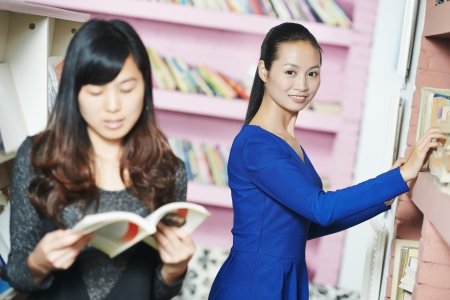 self study: young chinese student girl with book in library