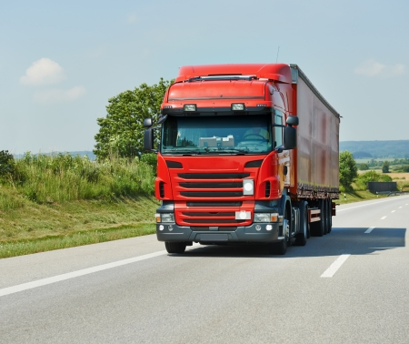 haul: red lorry with trailer on highway Stock Photo