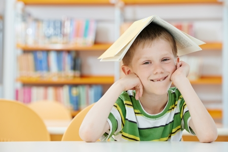 erudition: young boy with book in library
