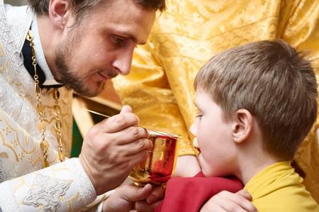 eucharistie: Orthodoxe Euharist cérémonie Priest rend enfant communion avec le bol à l'église