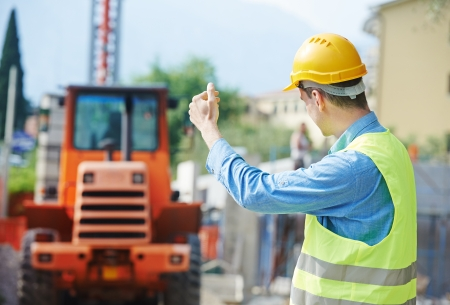 labourer: construction worker in safety protective work wear ruling construction machinery loader at building area Stock Photo