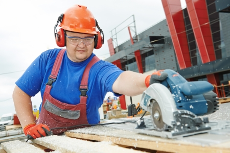 mounter: Male builder working with power tool circular saw machine cutting plastic parts at construction site