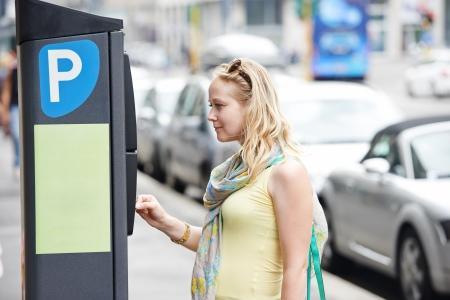 parking facilities: Mujer mujer joven que paga por aparcar en la calle