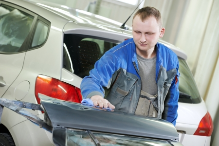 repairman worker in automotive industry wiping car body painting or repaint at auto repair shop photo