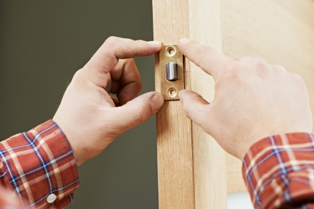 deadbolt: Two worker hands of carpenter at lock installation into wood door