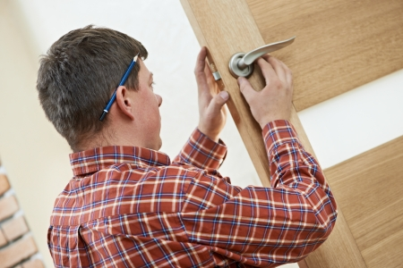 Male worker handyman carpenter at lock installation into wood door photo