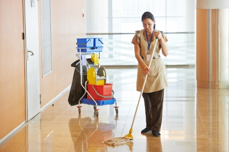 Female cleaner maid woman worker with mop in uniform cleaning corridor pass or hall floor of business building photo