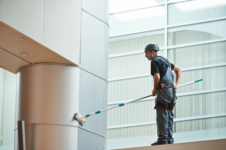 cleaning service: woman cleaner worker in uniform cleaning indoor window of business building