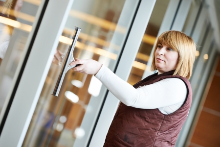charlady: woman cleaner worker in uniform cleaning indoor window of business building