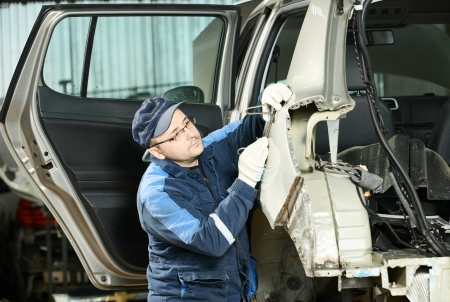car body: Young auto mechanic worker repair flatten and align metal car body in automotive industry