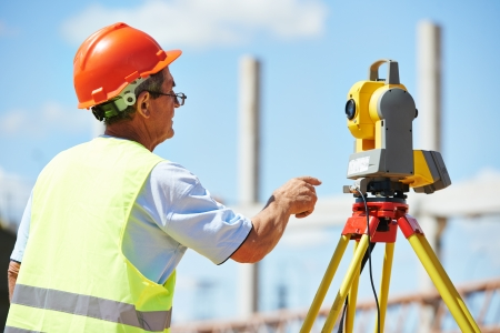 exact position: builder worker with theodolite transit equipment at construction site outdoors during surveyor work Stock Photo
