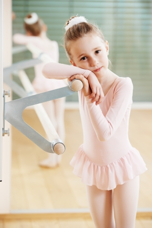 petite: Little girl in ballet suit at training exercise in front of mirror Stock Photo
