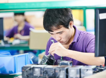 industry electronic: chinese male worker assembling production at line conveyor in china factory