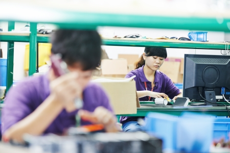 assembling: female chinese worker woman assembling production at line conveyor in china factory manufacturing Stock Photo