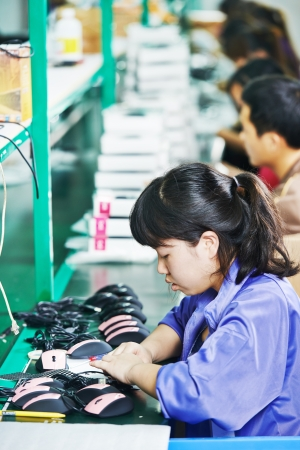 industry electronic: female chinese worker woman assembling production at line conveyor in china factory manufacturing Stock Photo