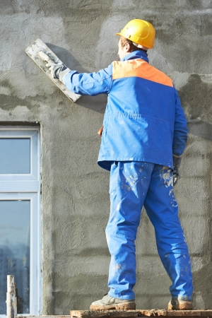 Male builder plastering exterior wall during industrial facade building with putty knife float photo