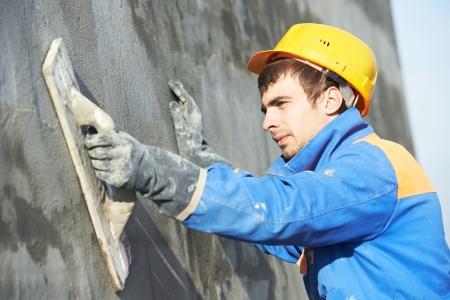 bedrijfshal: Jonge bouwer werknemer op de gevel bepleistering werk tijdens industrieel gebouw met plamuurmes vlotter Stockfoto