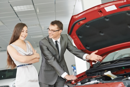 salesperson demonstrating new automobile car to young woman photo