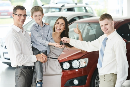 car dealers: At automobile sales centre. Car salesperson selling new automobile to young family with child boy