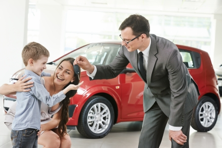 salesperson: At automobile sales centre. Car salesperson selling new automobile to young family with child boy