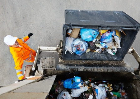 municipal: Worker of urban municipal recycling garbage collector truck loading waste and trash bin Stock Photo