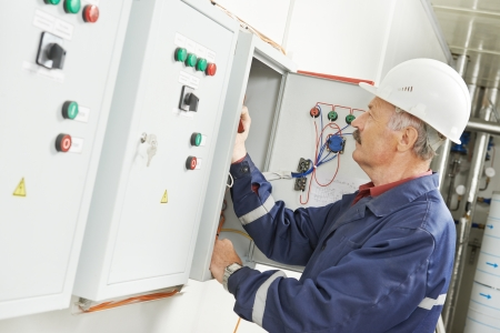 electrical cable: senior adult electrician builder engineer testing equipment in fuse box Stock Photo