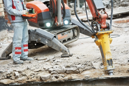 taskmaster: builder worker in safety protective equipment operating construction demolition machine robot Stock Photo