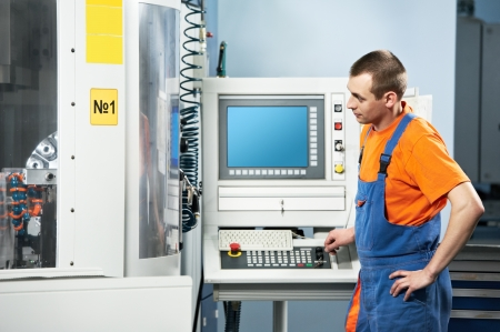milling center: tecnico meccanico che lavora al centro fresa CNC in officina strumento