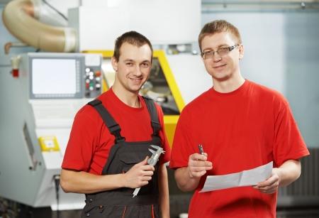 milling center: fabbricare i lavoratori tecnico parlano e misura dettaglio vicino a Centro di lavoro CNC fresatrice al workshop strumento
