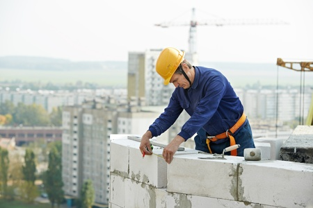 construction mason worker bricklayer working with limestone brick and measuring tape outdoors photo