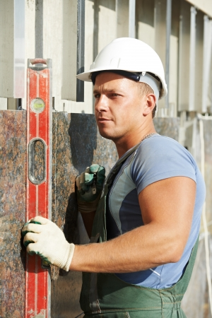 leveling: Plasterer builder worker with level examining granite stone marble facade works Stock Photo