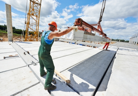 builder worker in safety protective equipment installing concrete floor slab panel at building construction site Stock Photo