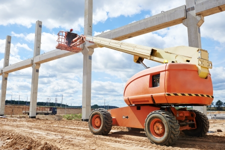 erector: builder worker putting cement mortar on concrete pole joint at construction site using lifting boom machinery