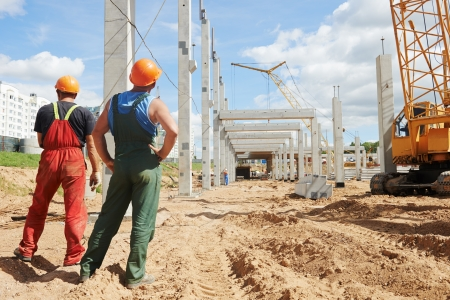 erector: two builder workers at construction site during concrete pole and beam installation