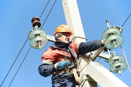 electrical wires: Electrician lineman repairman worker at climbing work on electric post power pole