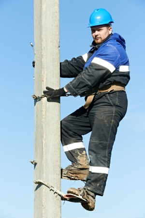 construction crew: Electrician lineman repairman worker at climbing work on electric post power pole