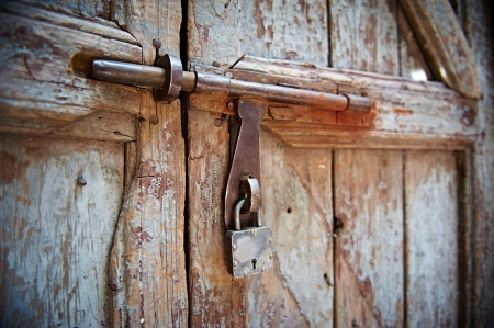 ancient prison: closed wooden door with padlock and metal locking bar